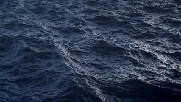 Fly over disturbed ocean water surface in slow motion, loopable
