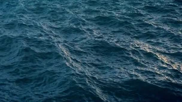 Fly over disturbed ocean water surface in evening time, loopable