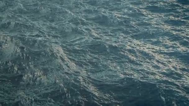 Fly over blue ocean surface in slow motion, loopable