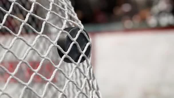 Hokejový puk letí do sítě na hokej desek s červeným pruhem. V pomalém pohybu