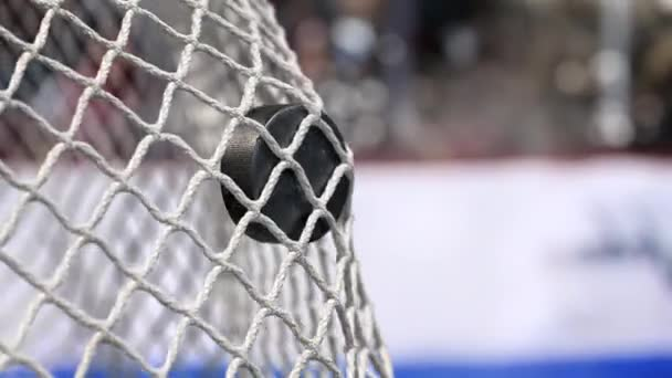 Hokejový puk letí do sítě na hokej desek s modrým pruhem. V pomalém pohybu