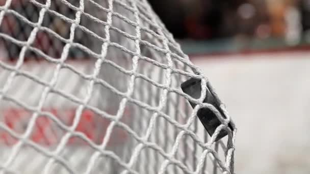 Hokejový puk letí do sítě na hokej desek s červeným pruhem. Pohyb na začátku je zrychlený pak pomalu