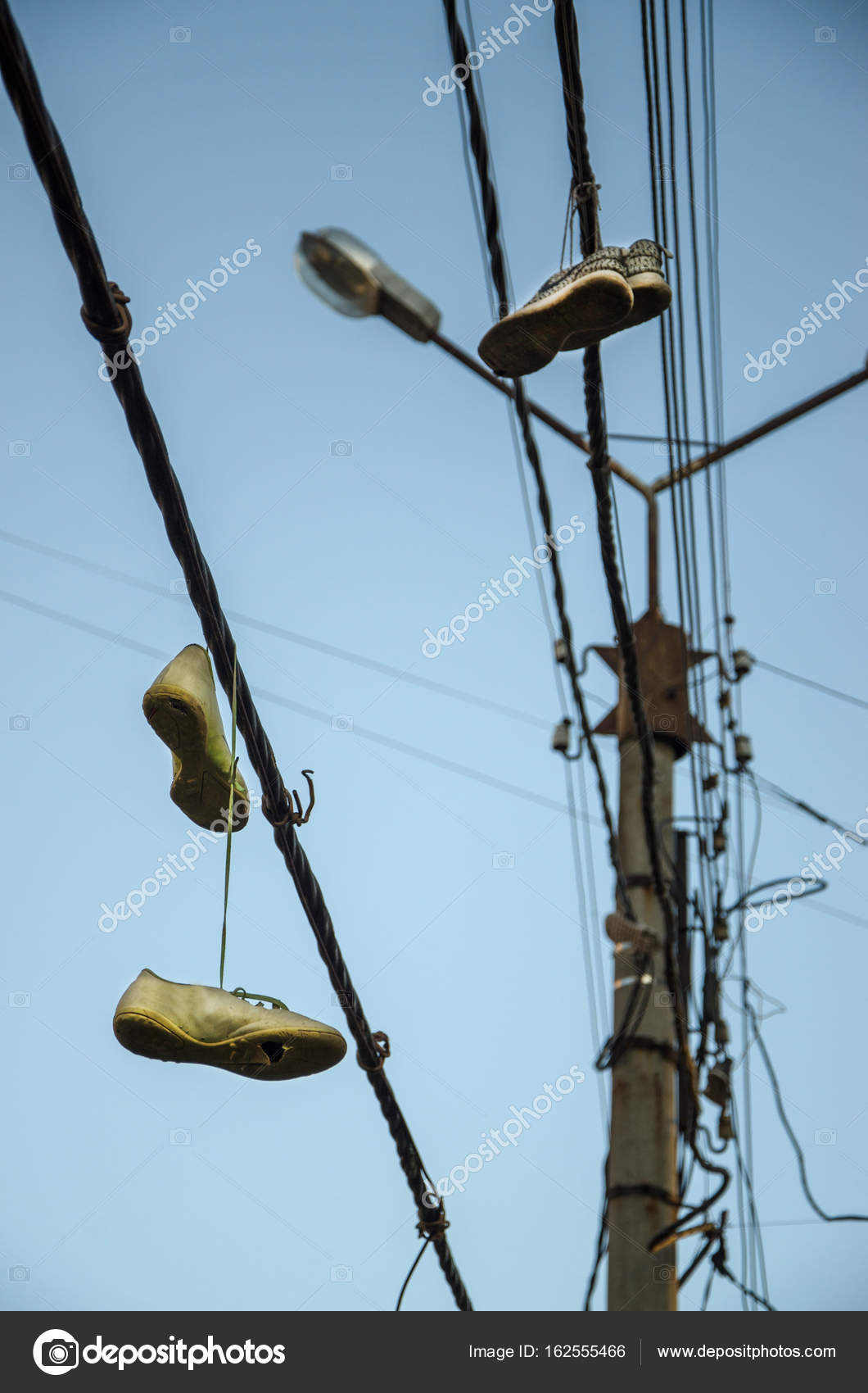 Sneakers hang on laces on electric wires on the street. — Stock ...