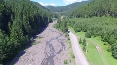Drone fly over the road near a mountain river in the woods