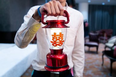 Groomsman Holding Red Traditional Lantern Lamp, with Chinese Character stickers meaning Double Happiness, in Chinese Wedding Ceremony as appropriate for marriage gift. Symbol of Male Childbearing.