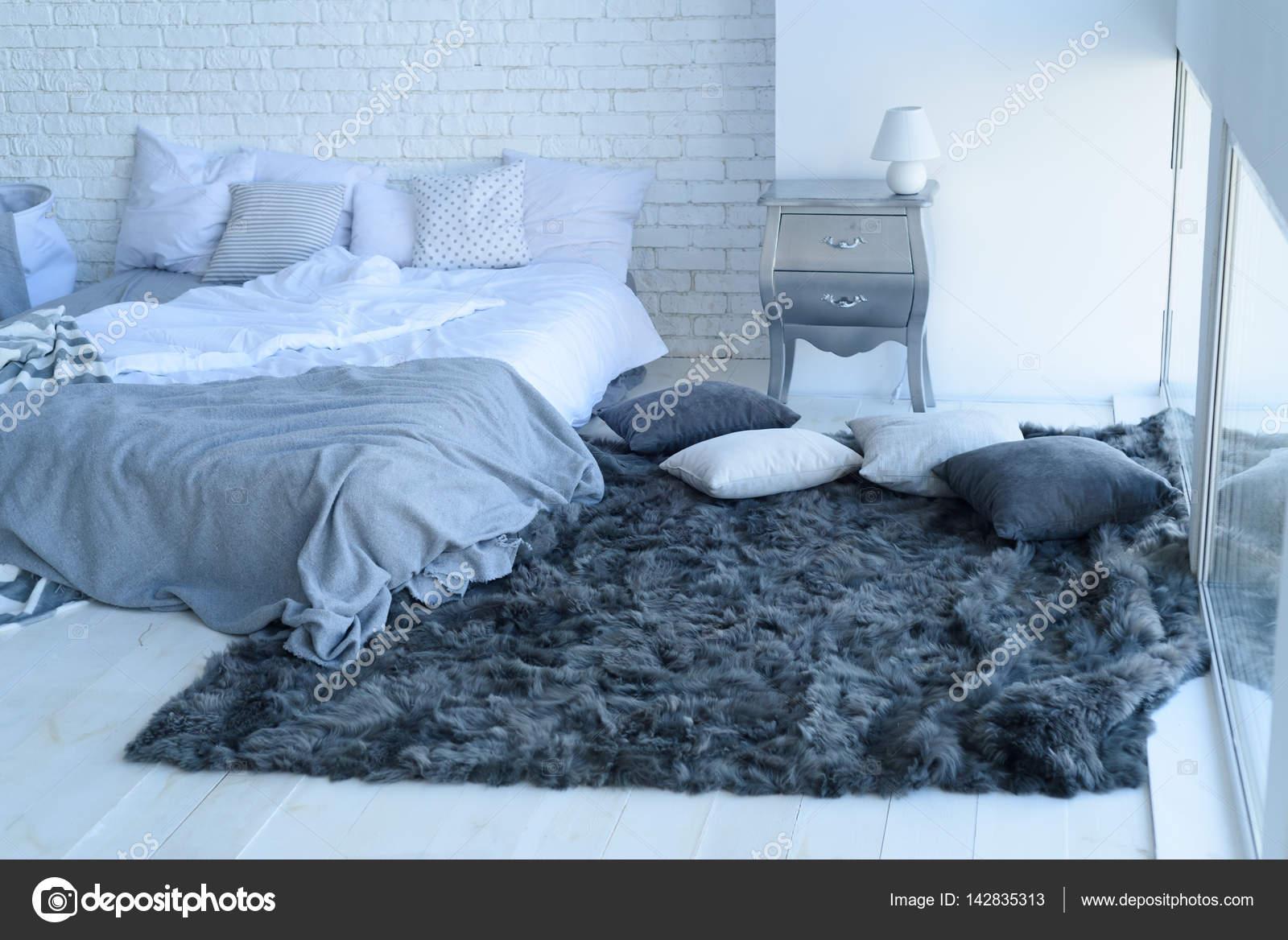 Interno camera da letto con un muro di mattoni con un letto e ...
