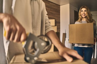 Attractive girl delivering a cardboard box to pack.