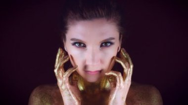 4k Studio Shot of a Golden Glittery Body Woman Posing with Hands