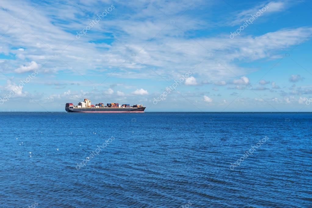 large container cargo ship on wide blue ocean