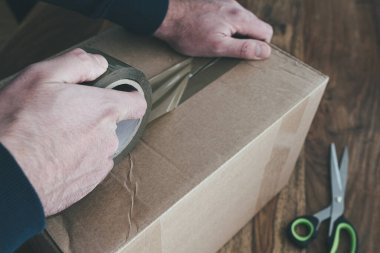 close-up of person sealing up shipping box with parcel tape