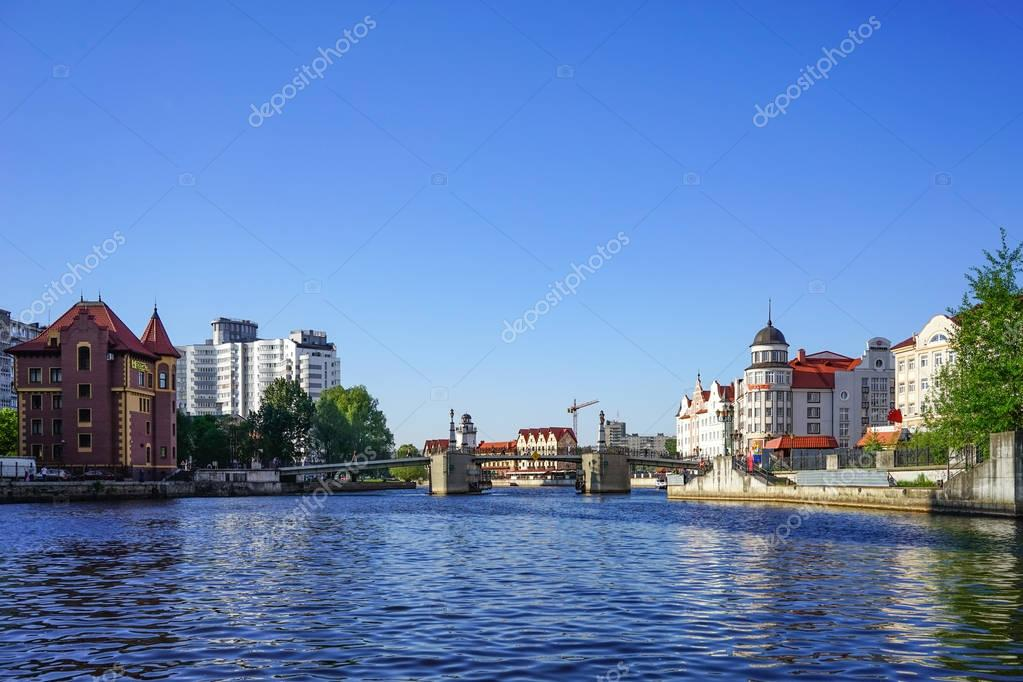 The modern landmark of the city with the lighthouse and buildings in the old style on the banks of the Pregolya river.