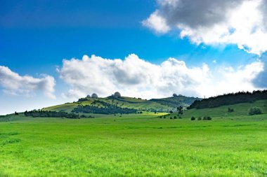 Natural landscape with a green field covered with grass under the blue sky with clouds.