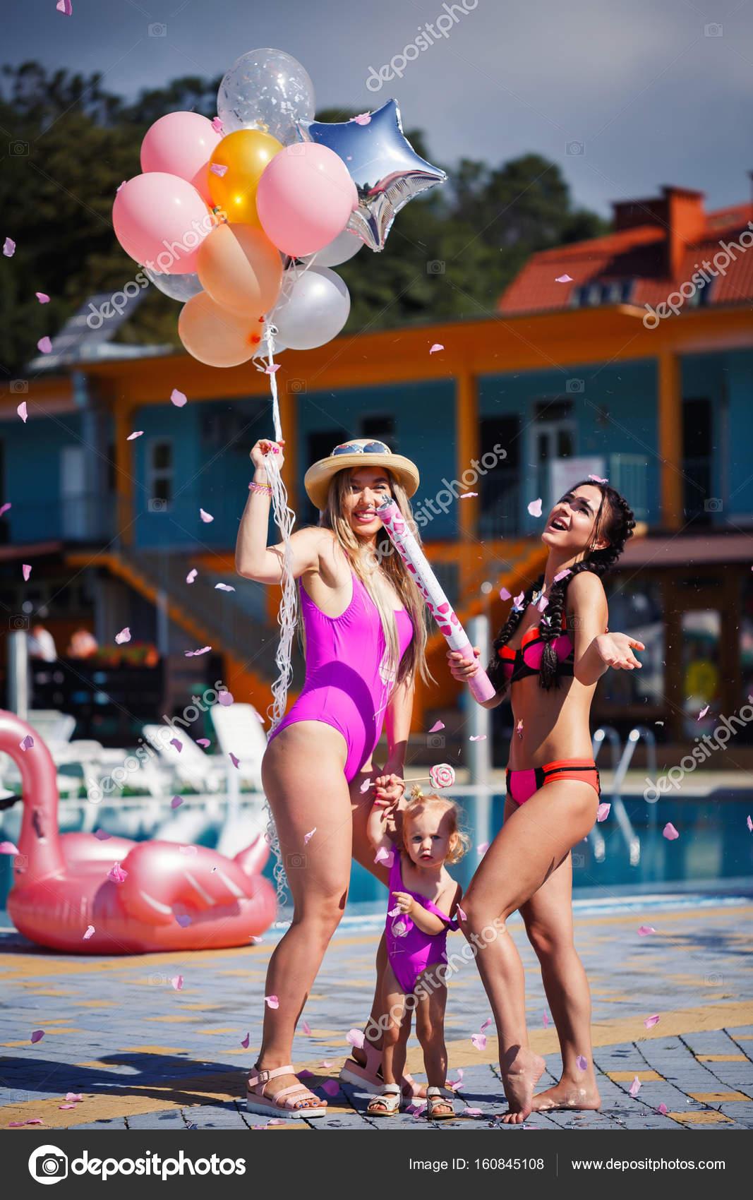 Due donne con un bambino in costumi da bagno luminosi e palloncini ...