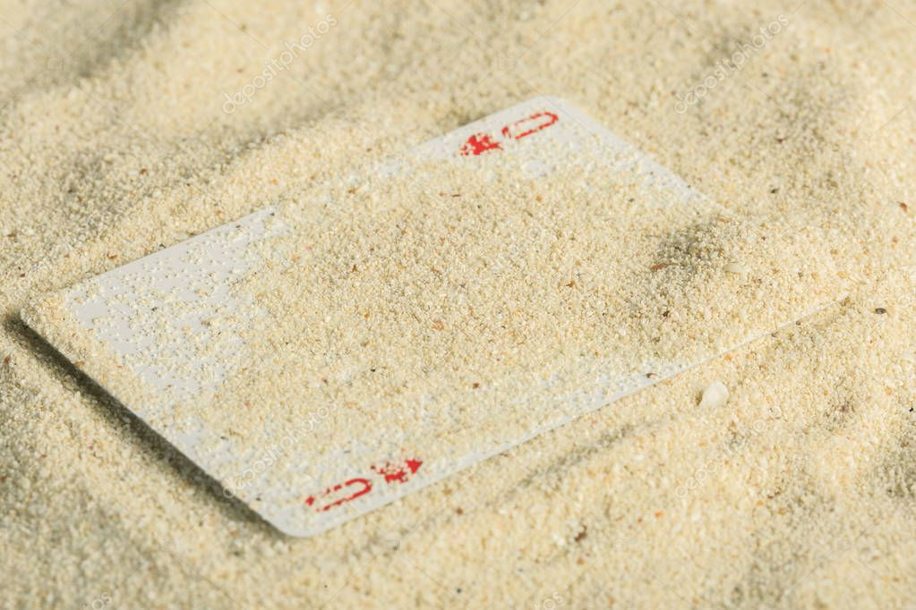 Poker playing cards buried in a sand dune