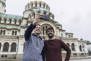Two young tourists taking photos with their mobiles in Sofia. Bulgaria