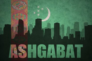 abstract silhouette of the city with text Ashgabat at the vintage turkmenistan flag background