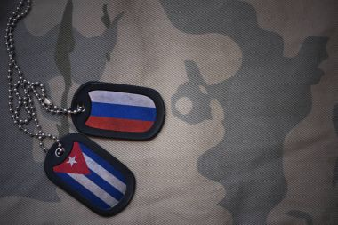 army blank, dog tag with flag of russia and cuba on the khaki texture background. military concept