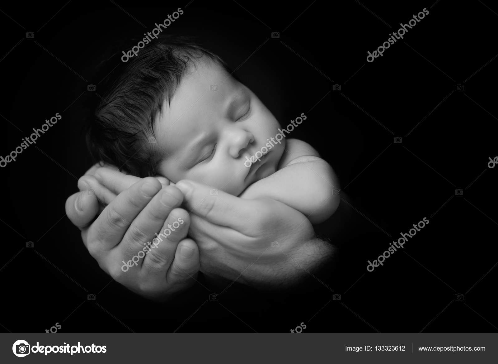 Newborn baby taken closeup in fathers hand black and white stock photo