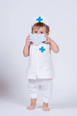 Girl child in a face mask, playing a nurse