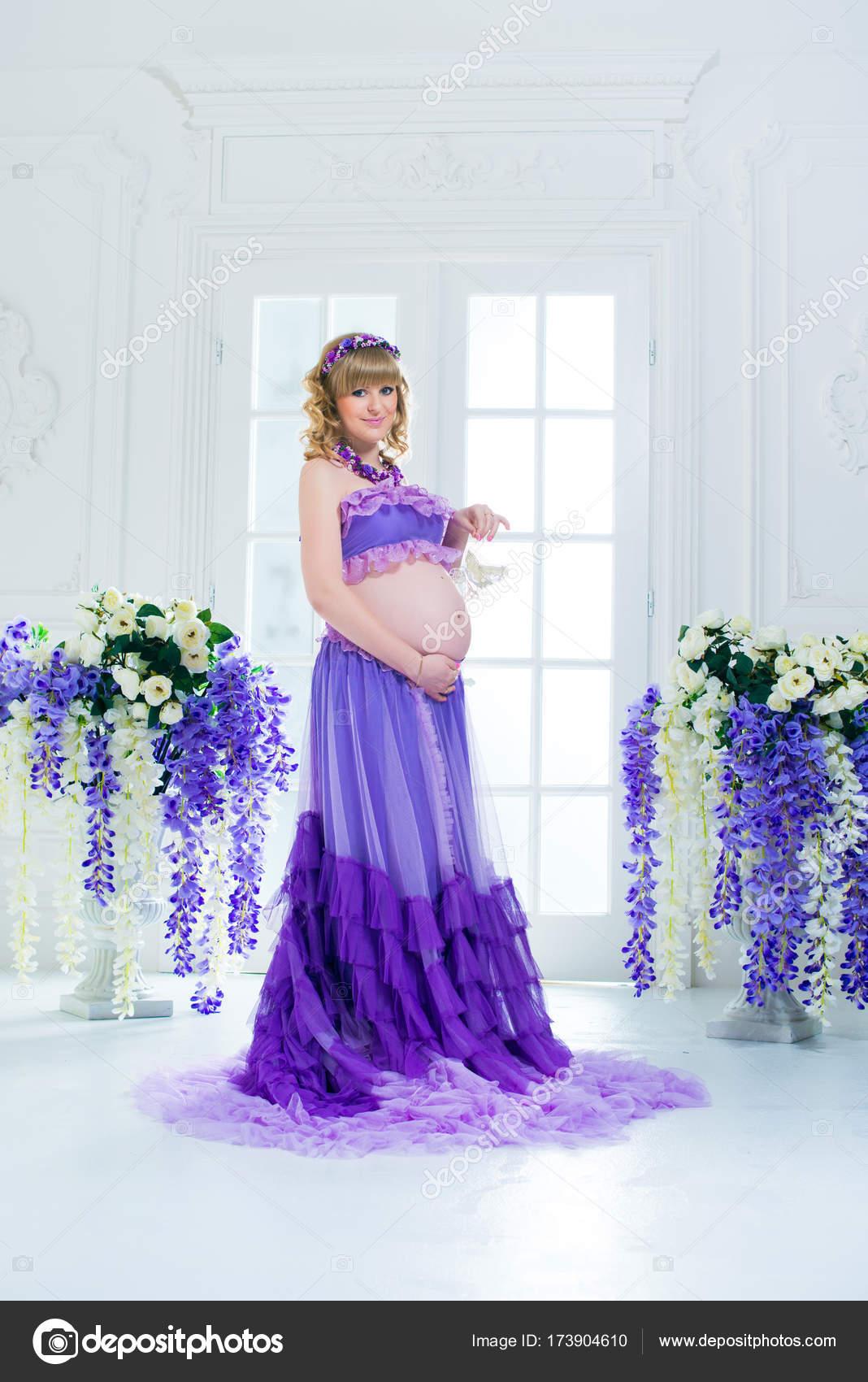 7c19d4842 Una feliz mujer embarazada en una falda larga púrpura plantea en el estudio  sobre un fondo de flores — Foto de ...