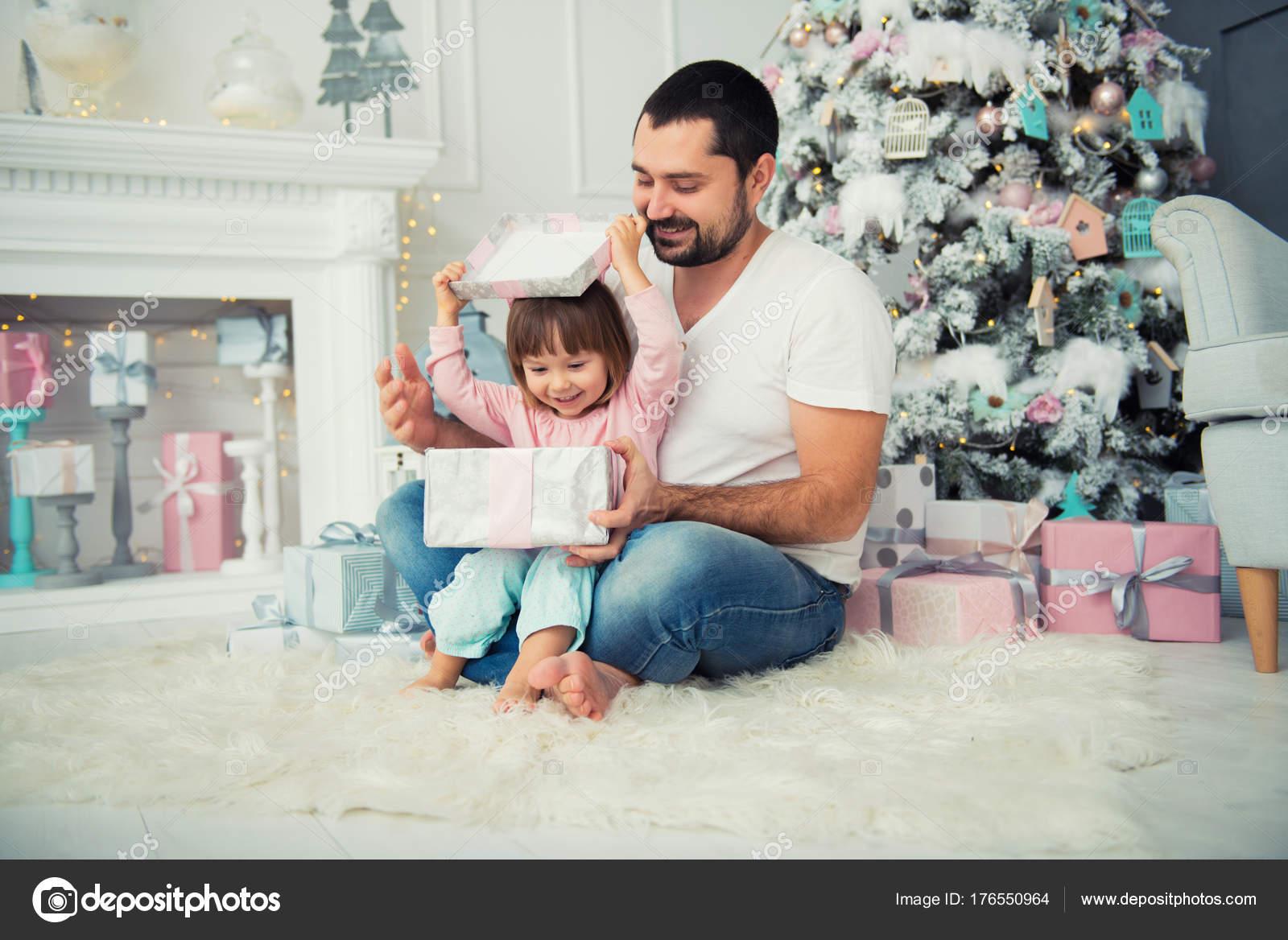 Vater und Tochter sitzen und öffnen ein Weihnachtsgeschenk in der ...