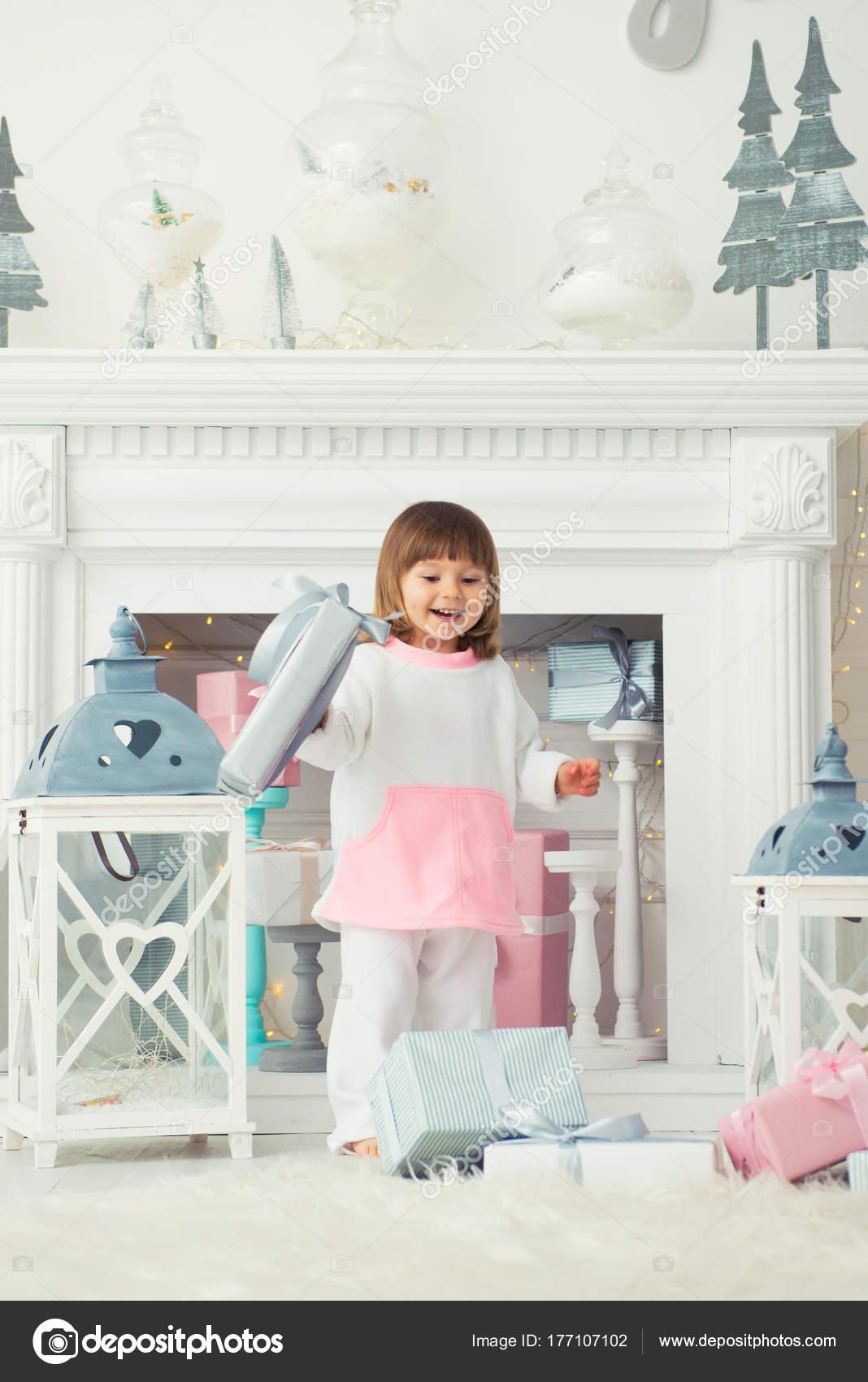 Ein glückliches lächelndes Mädchen steht mit Weihnachtsgeschenke in ...