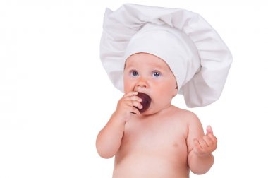 A small child is eating plums in a chef suit on a white background.