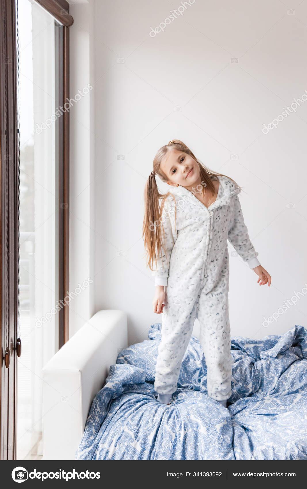 ein mädchen hellgrauen pyjama steht auf dem bett das kind