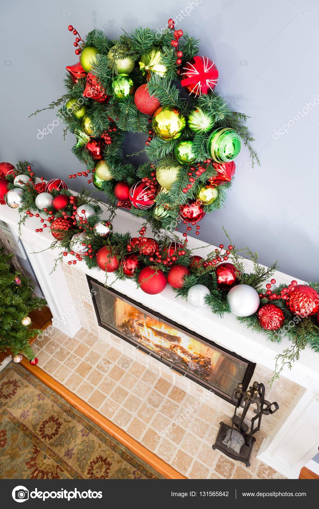 Traditionelle Bunte Weihnachten Kranz Hängen über Dem Kamin Und Dem Kaminsims  Dekoriert Mit Einem Kranz Von Roten Und Weißen Kugeln Mit Dunkelgrünem  Laub, ...