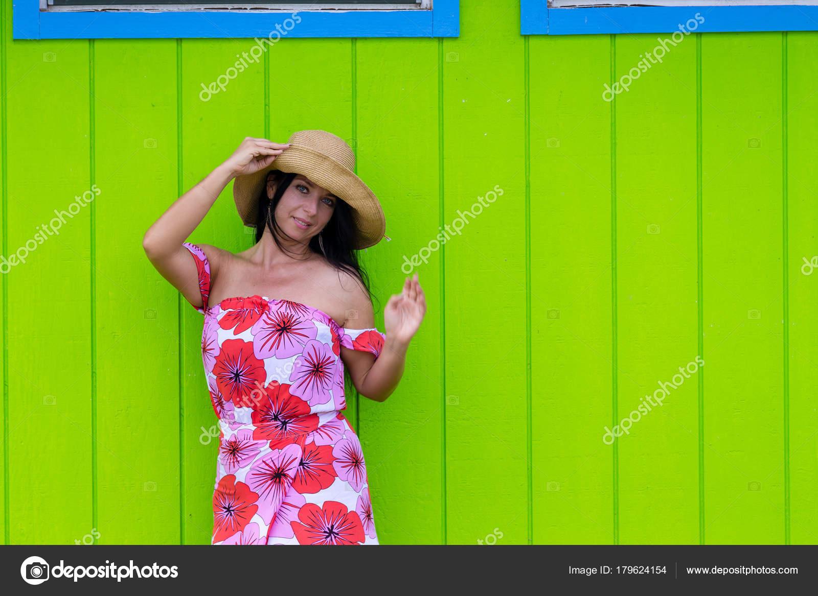 Donna graziosa in un cappello di paglia e vestito floreale rosso colorato  che propone contro una parete di legno verde in Hawaii agitando la mano a  fianco ... 675c6de91365