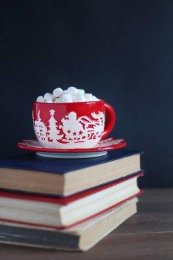 Christmas mug with marshmallows on a pile of books