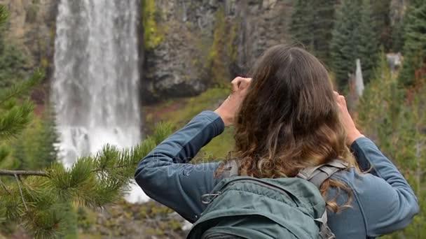 Tourist taking picture of Tumalo Falls Oregon