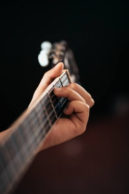 close-up of hand playing on guitar