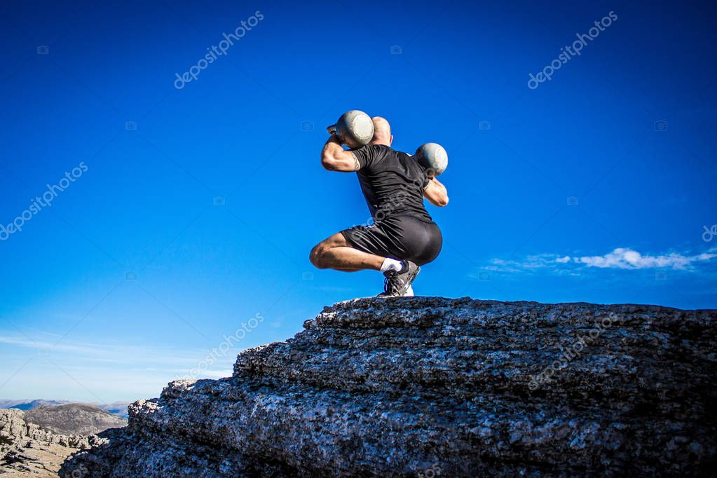 Man with kettlebells on the edge of a mountain