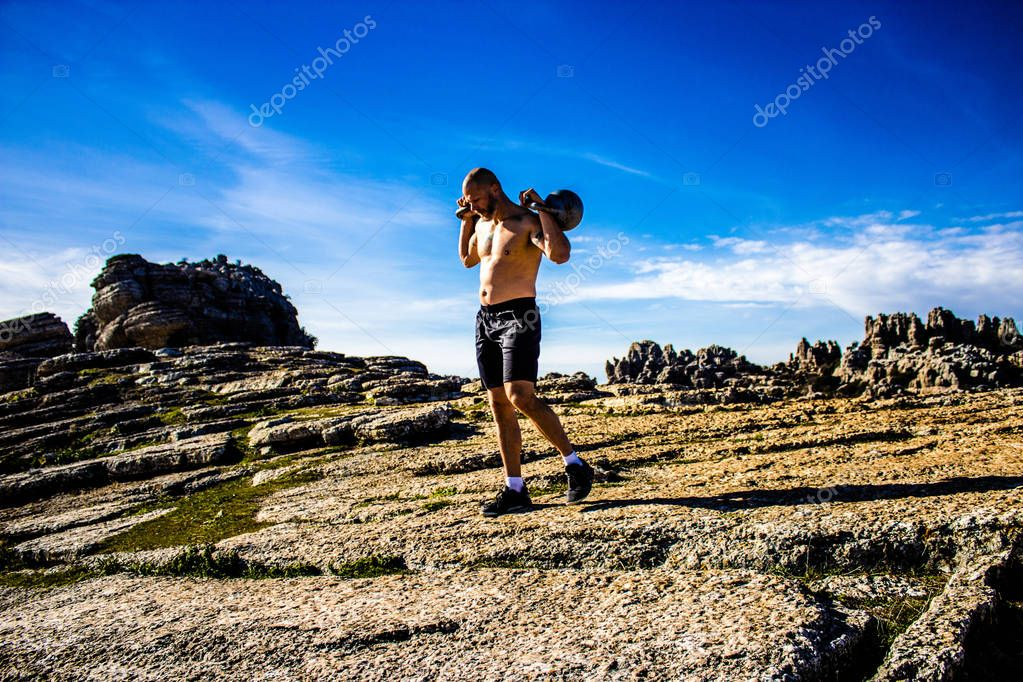 Man with no shirt holding two kettlebells on top of a mountain