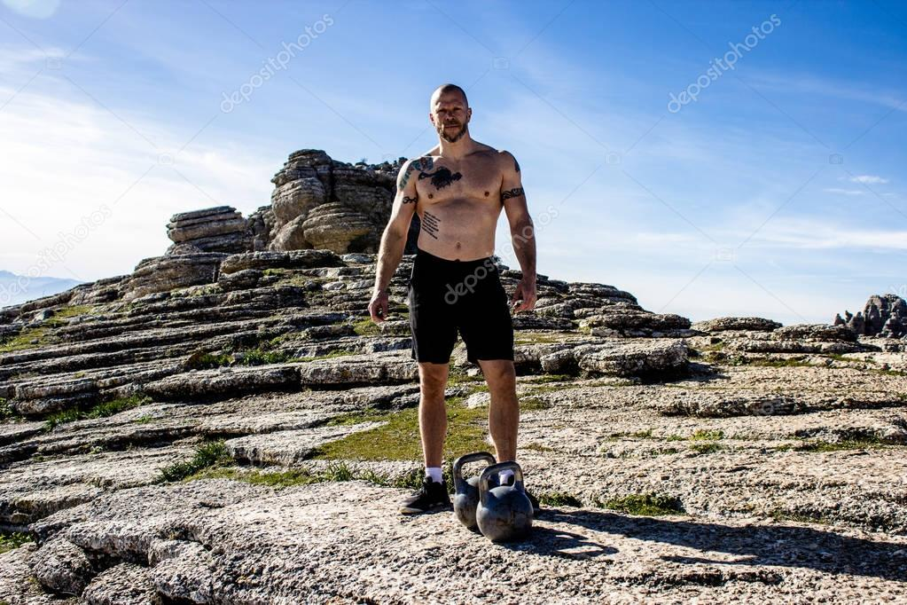 Male without a shirt and kettlebell on top of mountain