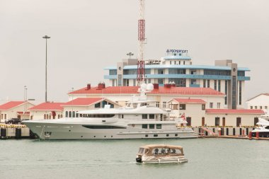 Large boat and small boat on the background of the building of Rosmorport Sochi
