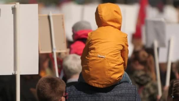 Demonstranten gehen mit dem Kind auf einer Kundgebung auf einer Straße der Stadt