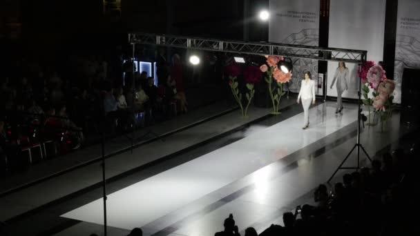 Modenschau Design weibliche Kleidung Frau auf dem Podium Nahaufnahme Scheinwerfer Bühne 4K.