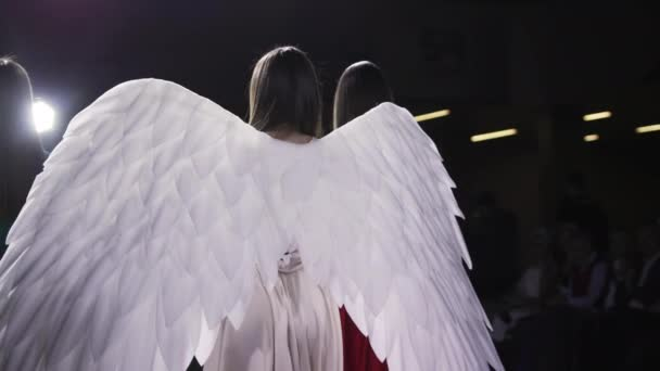 Beauty girl angel costume white wing close up walk on catwalk fashion outfit 4K.