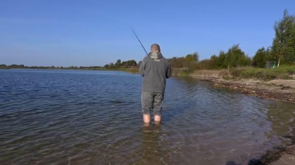 Horgász a halászati rúd a vízben