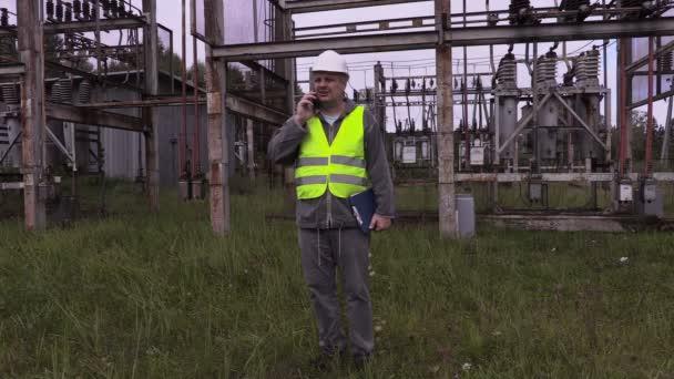 Elettricista con la cartella utilizzando smartphone nella sottostazione elettrica