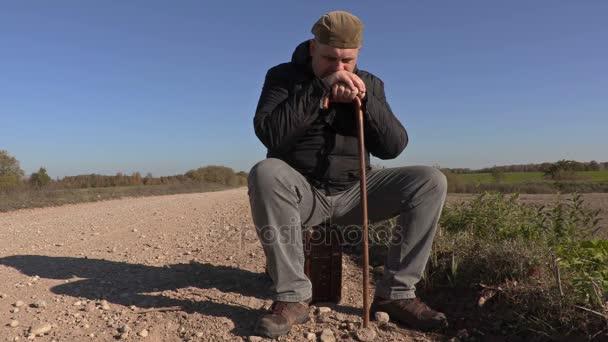 Magányos ember ül a bőröndöt a vidéki road mankó