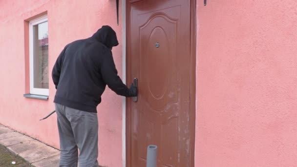 Lupič s páčidlem snaží otevřít dveře a dívat do kamery