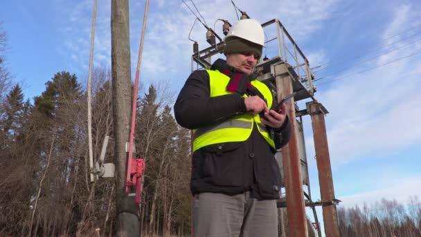 Elektrikář technik pomocí tabletu v blízkosti elektrického vedení a transformátor