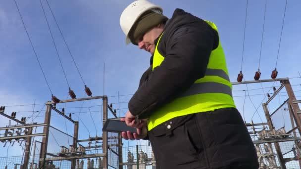 Elektrikář technik pomocí tabletu u rozvodny a walking away