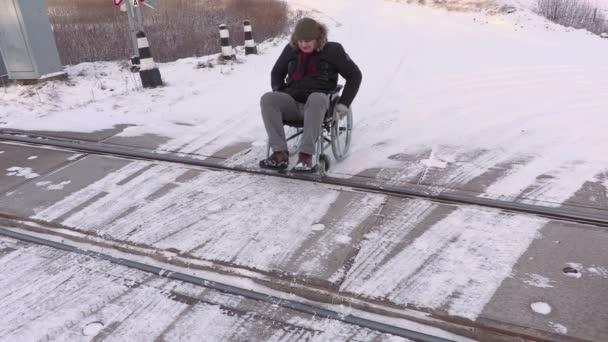 Postižený člověk na vozíku na železniční přejezd