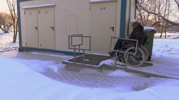 Postižený člověk na vozíku jednotce blízko veřejné WC
