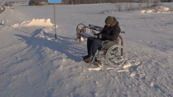 Postižený člověk na vozíku mluvit pomocí tabletu v blízkosti autobusové zastávky