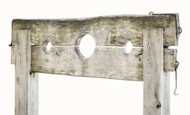 Wooden medieval pillory on white